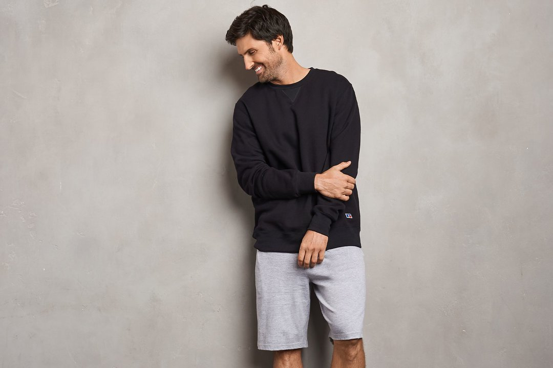 Man wearing Russell Athletic sweatshirt with shorts.
