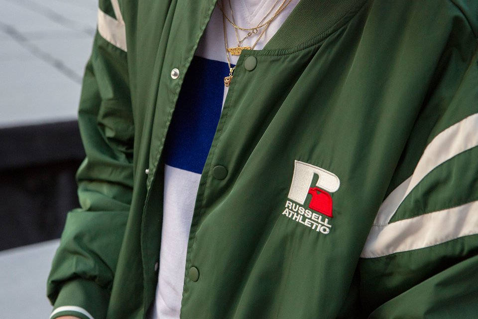Closeup picture of a person wearing a Russell Athletic bomber jacket.