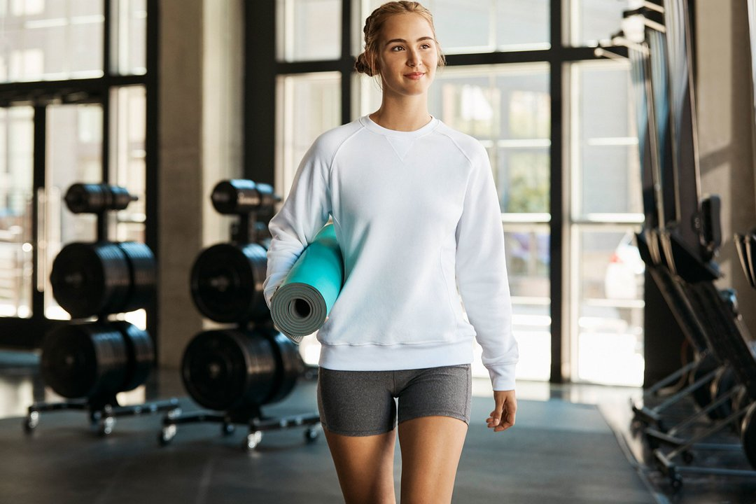 Woman posing wearing Russell Athletic sweatshirt with gym shorts.