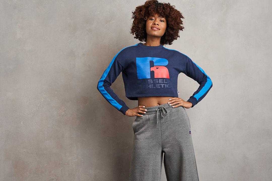 Woman posing wearing Russell Athletic sweatshirt.