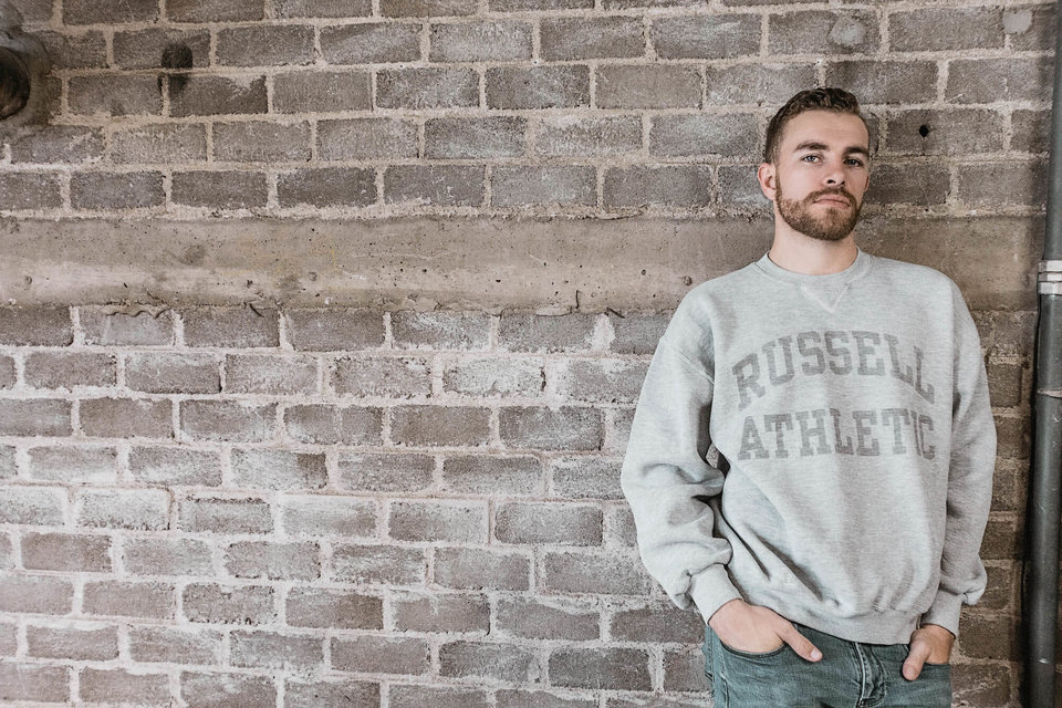 Man in Russell Athletic sweatshirt leaning on a brick wall.